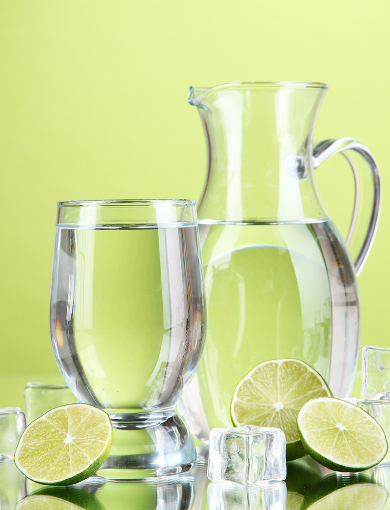 Glass pitcher of water and glass on green background